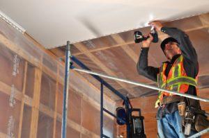 Construction worker installing Octaform Quickliner on a ceiling.